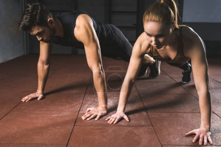 Young sportswoman and sportsman doing plank in sports hall
