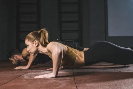 Side view of young athletes doing push ups in gym