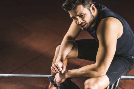 Tired young sportsman sitting on barbell in gym