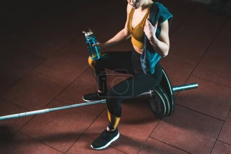 Cropped image of young sportswoman with towel and bottle sitting on barbell in gym