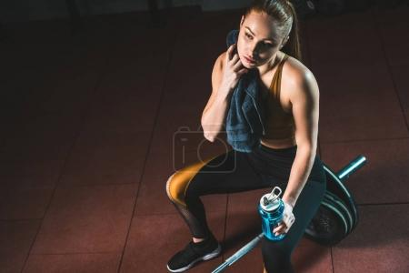 Young sportswoman wiping neck by towel and sitting on barbell in gym