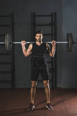 Front view of young sportsman holding barbell on shoulders in gym