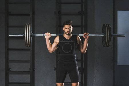 Young sportsman holding barbell on shoulders in gym