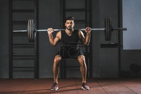 Photo for Sportsman doing exercise with barbell on shoulders in gym - Royalty Free Image