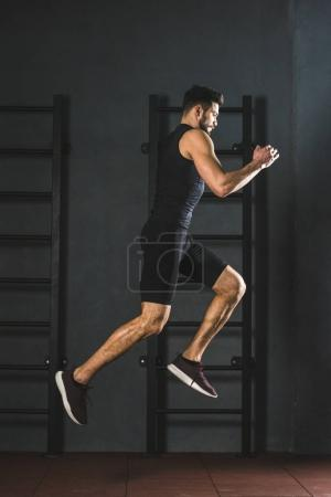 Young jumping sportsman doing cardio exercise in gym