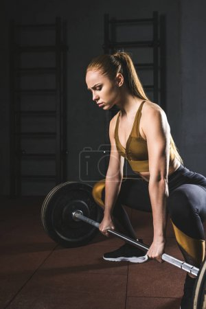 Young female bodybuilder preparing to raise barbell in gym