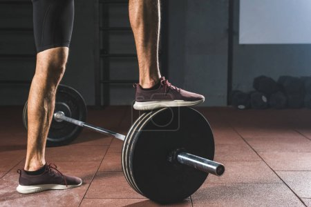 Cropped image of sportsman standing on barbell  in gym