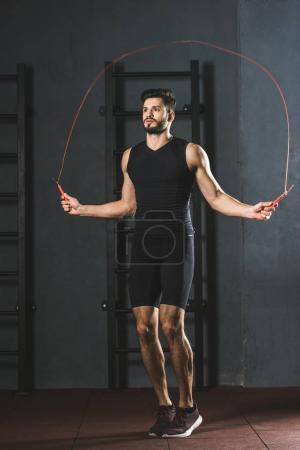 Photo for Young sportsman doing jump rope workout in gym - Royalty Free Image