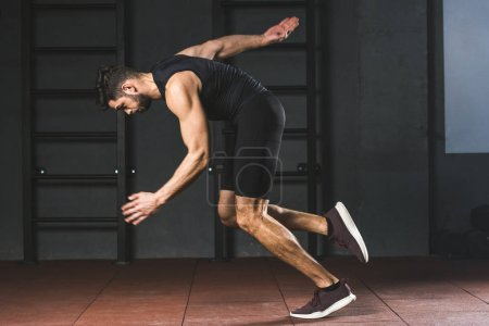 Side view of young sportsman running in sports center
