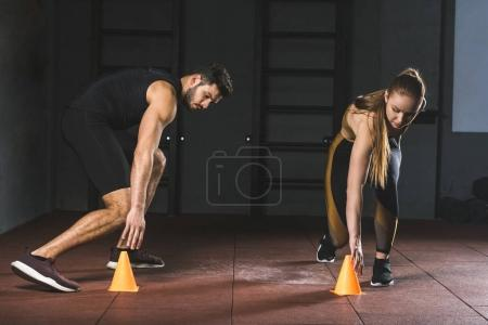 Young athletes running and touching training cones in sports center