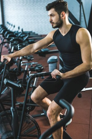 Young sportsman doing workout on exercise bike in sports center