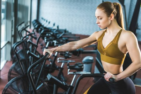 Young sportswoman doing workout on exercise bike in sports center