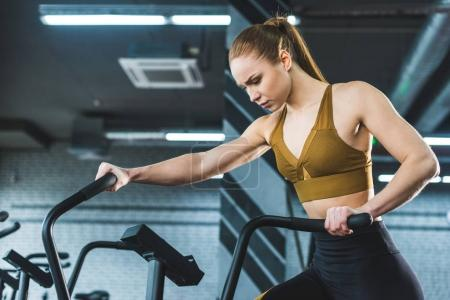Sportswoman doing workout on exercise bike in sports center