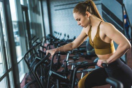 Photo pour Vue latérale de la sportive faisant de l'entraînement sur vélo d'appartement dans le centre sportif - image libre de droit