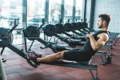 Side view of sportsman doing exercise on rowing machine in sports center
