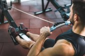 Cropped image of young sportsman doing exercise on rowing machine in sports center