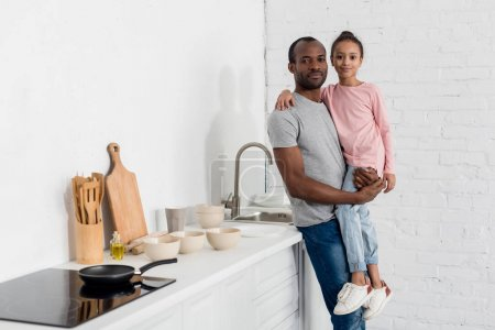 happy african american father holding his daughter at kitchen and looking at camera