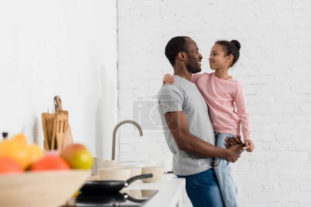 Photo for Handsome young father holding his daughter at kitchen - Royalty Free Image