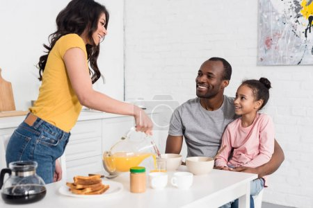 Photo for Woman pouring orange juice into glass for husband and daughter - Royalty Free Image