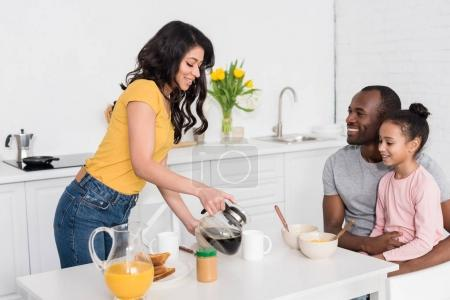 woman pouring coffee into cups for husband and daughter