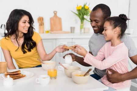 smiling young family having healthy breakfast on kitchen together
