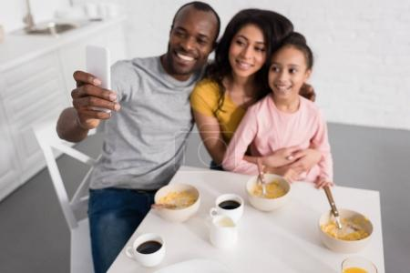 smiling young family taking selfie on kitchen while having breakfast