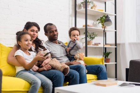 junge Familie schaut gemeinsam Fernsehen im Wohnzimmer