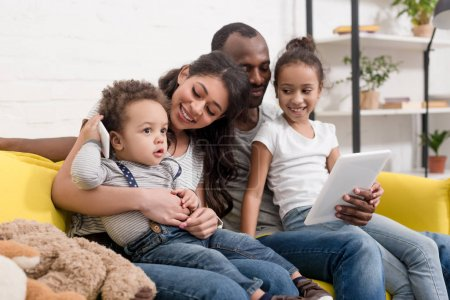 happy young family spending time together with devices at home
