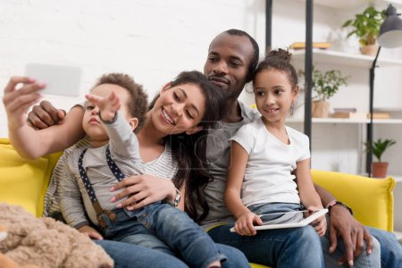 happy young family taking selfie on couch at living room