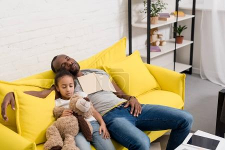 father and daughter sleeping together on couch after reading fairytale