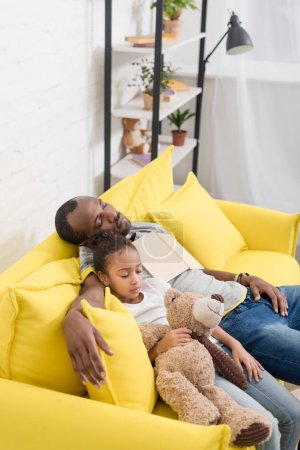 father and beautiful daughter sleeping together on couch after reading fairytale