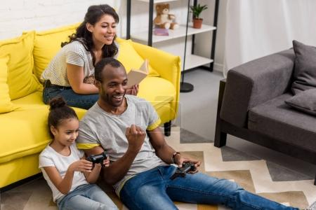 emotional father and daughter playing video games while mother sitting on couch