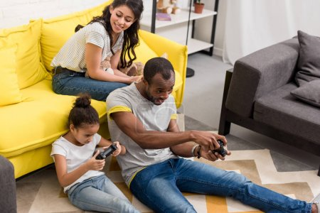 excited father and daughter playing video games while mother sitting on couch