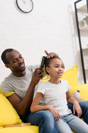 father combing hair of daughter while sitting behind her on couch