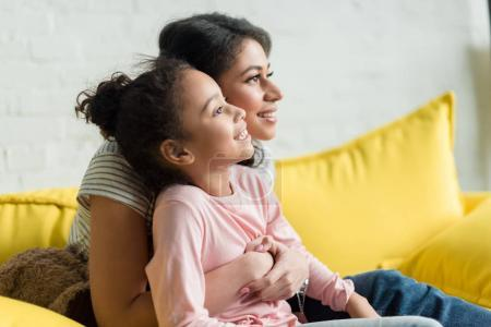 young happy mother and daughter embracing her daughter on couch at home