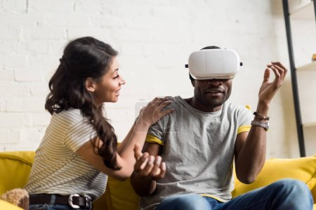 smiling african american woman sitting near expressive boyfriend while he wearing virtual reality headset on couch at home