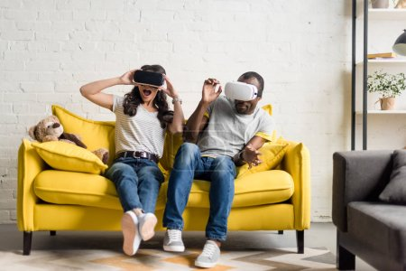 frightened african american couple in virtual reality headsets sitting on couch