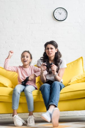 emotional mother and daughter playing video games at home on couch