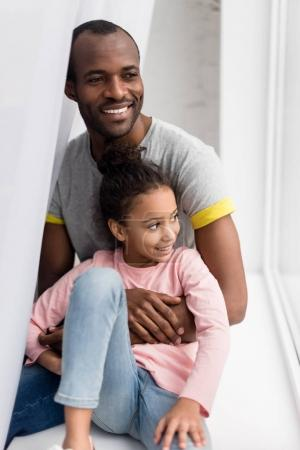 Photo for Smiling african american father and daughter sitting on windowsill - Royalty Free Image