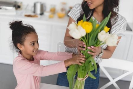 cropped shot of mother and beautiful daughter putting flowers into vase
