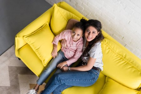 top view of mother and daughter sitting on couch together and looking at camera
