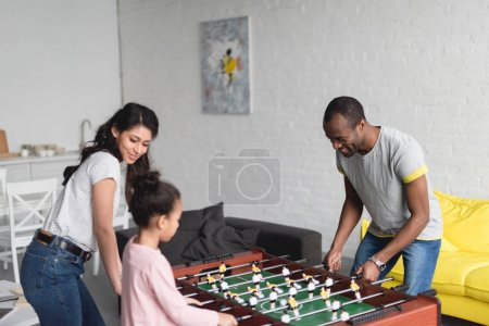 african american family playing table football together at home