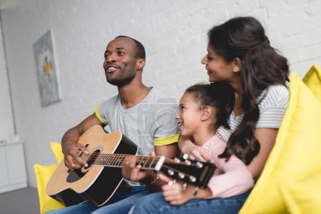 man playing guitar and singing for wife and daughter at home