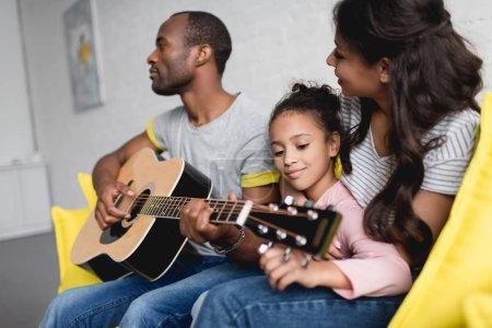 Photo pour Homme jouant de la guitare pour la femme et sa fille à la maison - image libre de droit