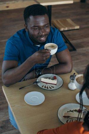 Photo pour Vue grand angle souriant afro-américain avec tasse de café en regardant la petite amie dans le café-restaurant - image libre de droit