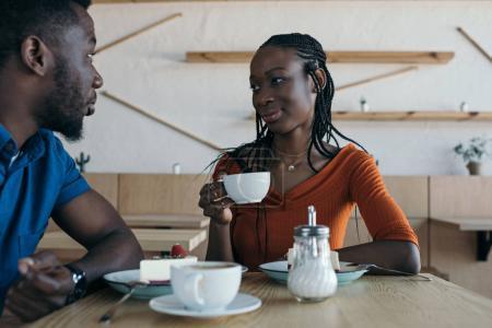couple afro-américain assis à table avec les tasses de café et des desserts au café