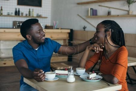 Photo for Happy african american couple sitting at table with cups of coffee and desserts in cafe - Royalty Free Image