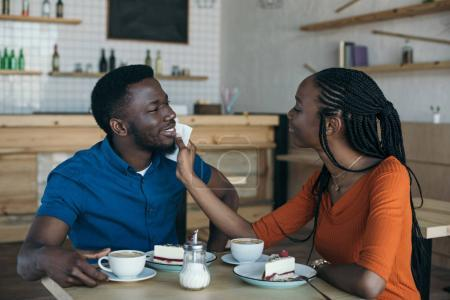 careful african american woman cleaning boyfriends face with napkin at table in cafe