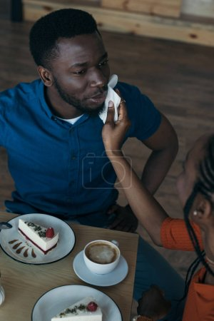 high angle view of careful african american woman cleaning boyfriends face with napkin at table in cafe