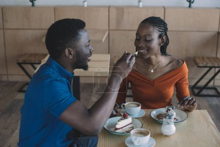 african american man feeding girlfriend with dessert on romantic date in cafe